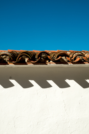 Roof tiles projecting shades on a whitewashed facade