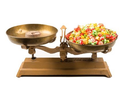 Colorful popcorn candy on vintage scales, an unhealthy food concept Stock Photo
