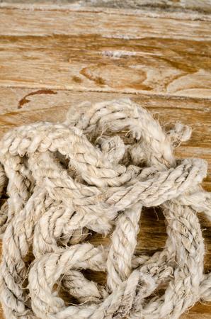 昔の木製の背景にロープをヒープします。