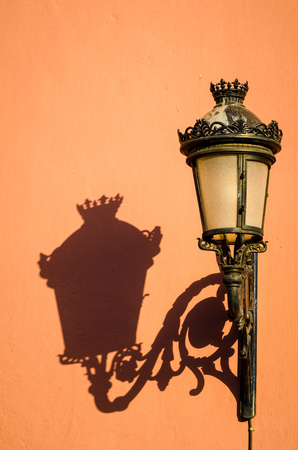 lamp shade: Cast irons street light casting a shadow on a Mediterranean old town house facade