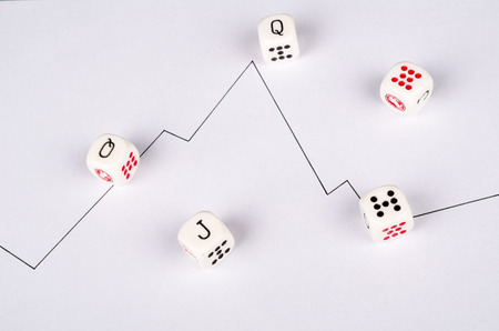 Dice scattered around a chart, a conceptual shot on the unpredictability of the stock market Фото со стока