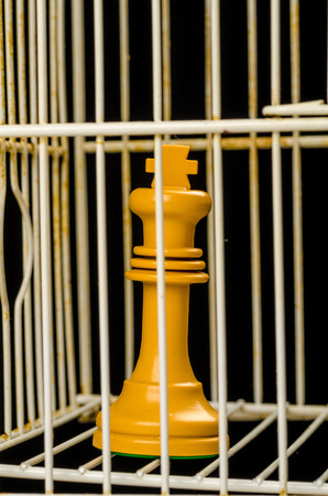 King behind prison bar, a political conflict concept Stock Photo