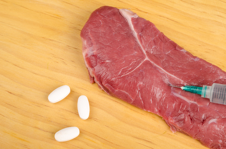 Hormones being injected in a beef steak, a conceptual food manipulation shot