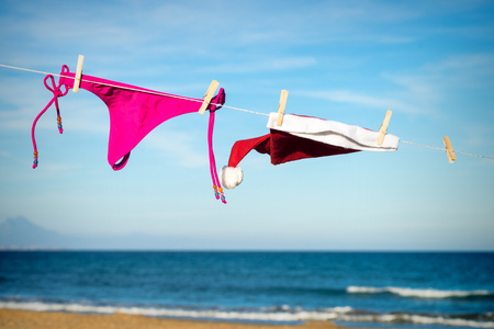 Bikini tanga and Santa hat drying on a sunny beach, a seasonal getaway concept
