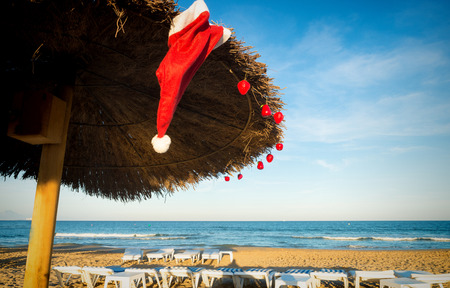 Christmas ornaments on a sunny resort beach, a concept on a wintertime getaway to warmer regions.
