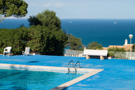 Sunny swimming pool with view over the Mediterranean coastline