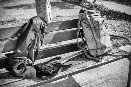 Guitar on a park bench, a street musician concept Editorial