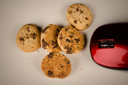 Mouse eating cookies, a funny technology concept Stock Photo