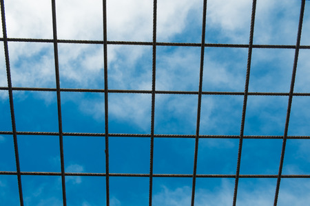 Ready steel rod structure on a building site against the background of the sky. 스톡 콘텐츠