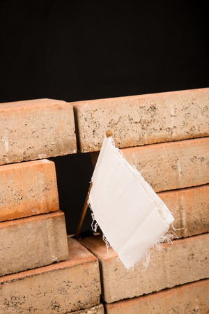White flag on a wall, a multiple concept both on overworking and on immigration Stockfoto