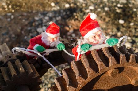 Santa in the cogwheels of consumerism, a concept 版權商用圖片
