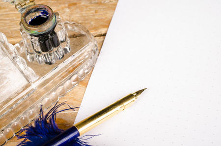 Dip pen in the shape of a quill on a document and next to an ink well