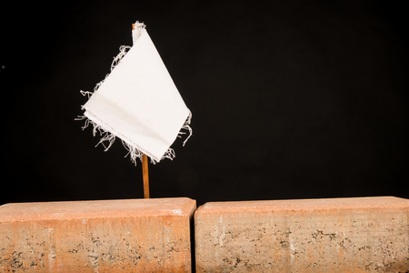 White flag on a wall, a multiple concept both on overworking and on immigration Reklamní fotografie - 114302459