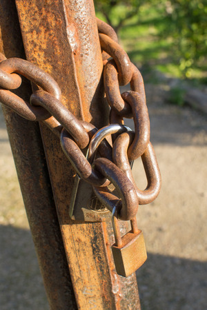 Oxidized chain and padlock on an old gate Stock Photo