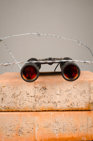 Spy glass atop of a wall, a concept on migratory issues in current politics