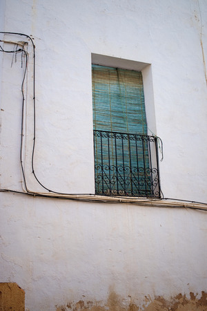 Weathered facade of an old Andalusian town house, window with green shutters