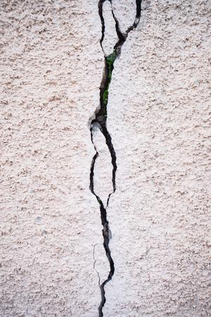 Huge crack on a whitewashed stucco wall