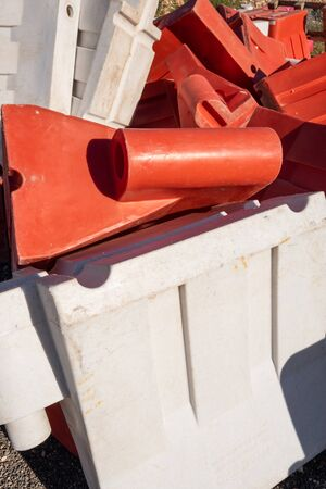 Disassembled links of a red and white plastic road barrier Imagens