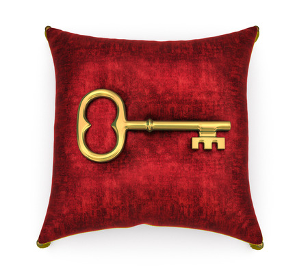 Golden key on royal red velvet pillow isolated on white background