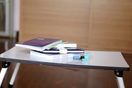 disorganized: A disorganized pile of books and clips on a small table. Located inside the bedroom Preparation for Reading