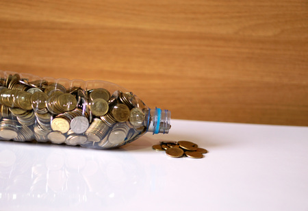 recycle plastic: Coins and recycle plastic bottle on the desk. Stock Photo