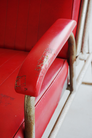 teared: Armrest of old red chair  in beauty salon.
