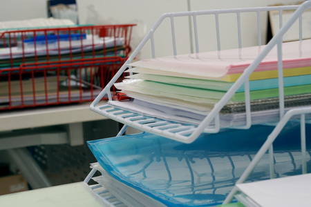Stack of document tray with document multicolor paper on desk in office and copy space.  Document equipment and business office concept.