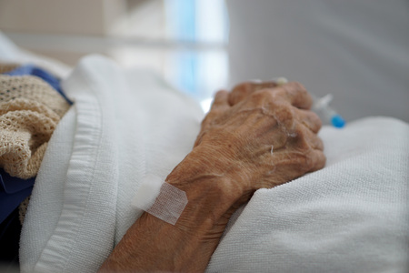 Closeup hand of sick elderly patient lying on the bed in hospital                               Stock Photo