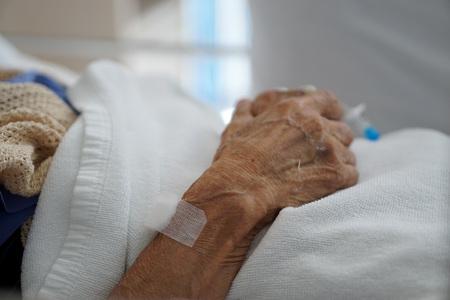 Closeup hand of sick elderly patient lying on the bed in hospital                               Foto de archivo
