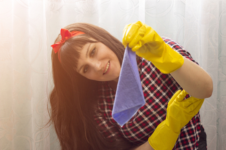 A brunette girl in yellow gloves holds a rag for cleaning Standard-Bild