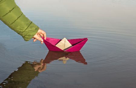 The girl is launching a red paper boat, close-up