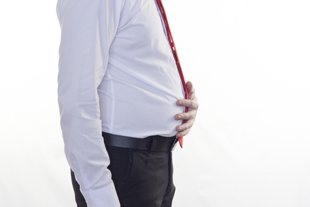 A man in a white shirt and red tie, a big belly holding his stomach, a white background Standard-Bild