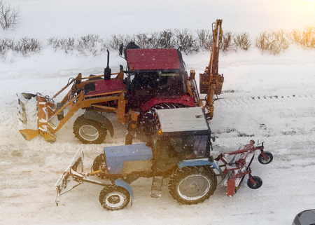 Red and blue tractor for snow cleaning. two tractors