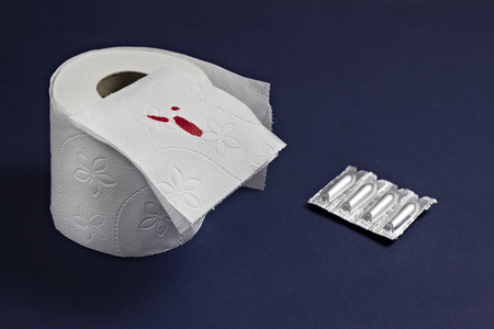 Toilet paper with blood and rectal suppositories against hemorrhoids, blue background