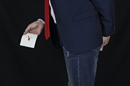 Man in suit holds toilet paper with blood, hemorrhoids, black background Stock Photo