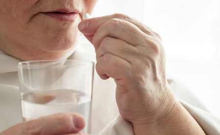 Elderly woman drinks a pill, glass of water, close-up