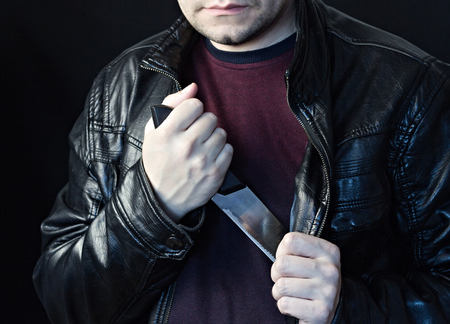 A man takes a knife out of a jacket, a black background