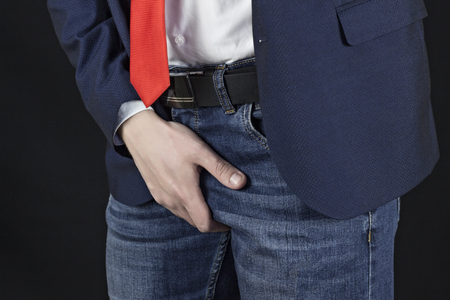 A man in a punch jacket and a necktie is a businessman holds on the groin, a black background Stock Photo