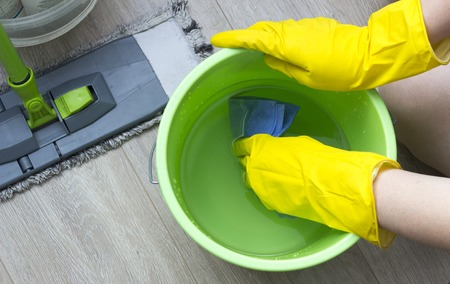 A girl in yellow gloves wets a rag in a bucket, cleaning equipment
