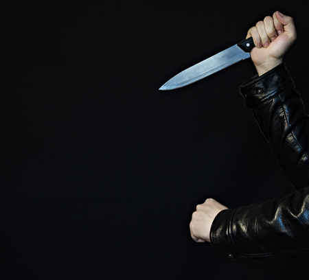 Male hands with a knife and fist on a black background, close-up