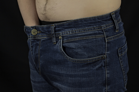 The man put his hand in his panties, black background, close-up