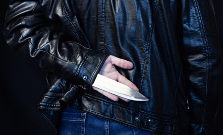A man in a leather jacket holds a knife behind his back, a black background