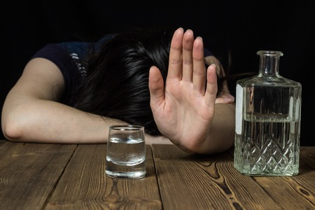 Drunk girl lies on the table, hand shows stop, black background, on table alcohol