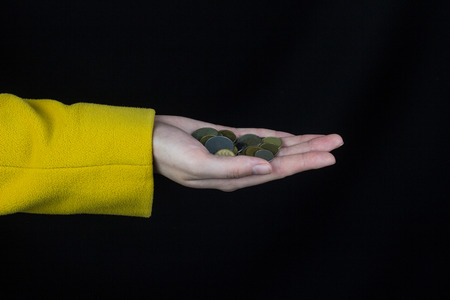 female hand in a yellow jacket holds a handful of coins, a black background Banco de Imagens