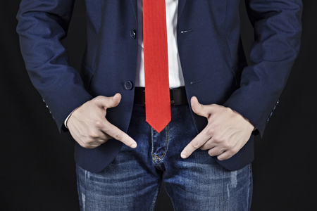 Man in suit shows with fingers on inguinal area, black background Stock Photo