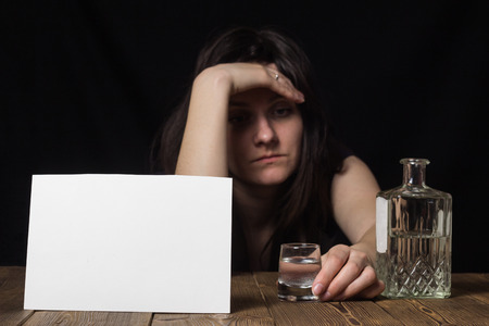 Sad girl sitting with a glass in her hand, bottle and alcohol, black background, clean sheet