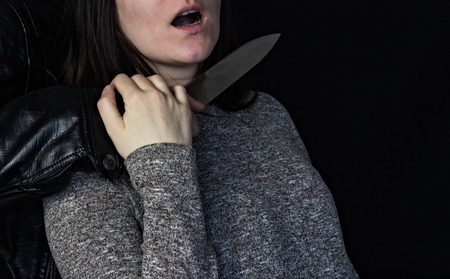 Man holding a knife at the girls throat, black background Banque d'images