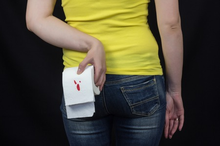 Girl with toilet paper with blood, hemorrhoids, black background, female