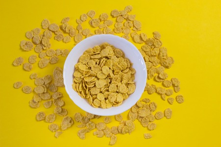 Corn flakes in a plate on a yellow background, nutrition