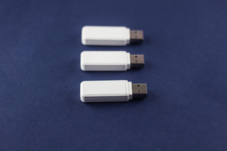 Three white flash drives on a blue background, close-up, connection 版權商用圖片